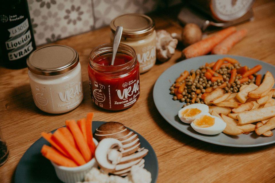 3 sauces en vrac sont posées sur le comptoir avec une assiette de crudités et à côté d'autres accompagnements