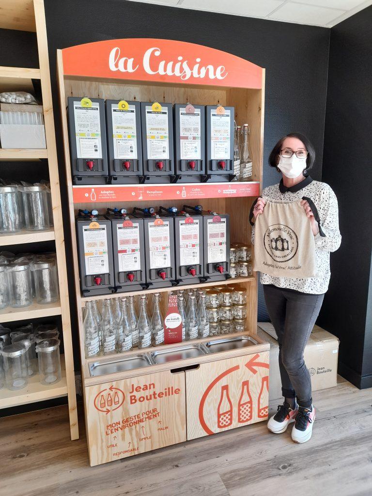 Sophie gérante de Mademoiselle Vrac Bruz se tient devant son rayon vrac liquide Jean Bouteille