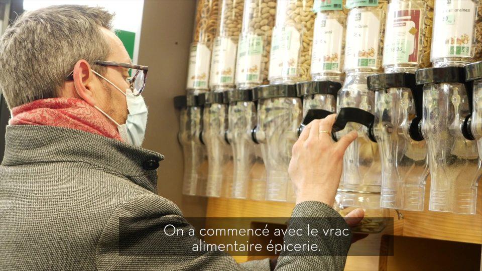 Un consommateur se sert de vrac sec dans les rayons vrac d'Harmonie Nature Biomonde à Lille.