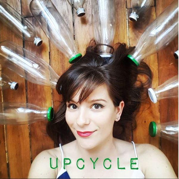 Portrait de Camille Chaudron ou Girl Go Green entourée de bouteilles en verre réutilisables